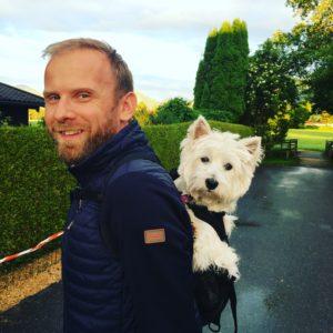 Mann mit Hund auf dem Rücken