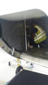 Mann im Frachtraum des Flugzeugs